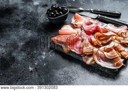 Set Of Cold Cured Italian Meat Ham, Prosciutto, Pancetta, Bacon. Black Background. Top View. Copy Sp