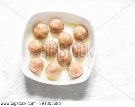 Raw Chicken Meatballs In A Baking Dish On A Grey Background, Top View. Cooking Baked Meatballs
