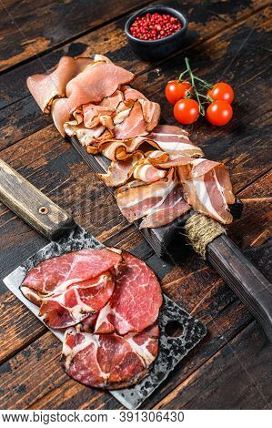 Set Of Cold Cured Italian Meat Ham, Prosciutto, Pancetta, Bacon. Dark Wooden Background. Top View