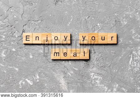 Enjoy Your Meal Word Written On Wood Block. Enjoy Your Meal Text On Cement Table For Your Desing, Co