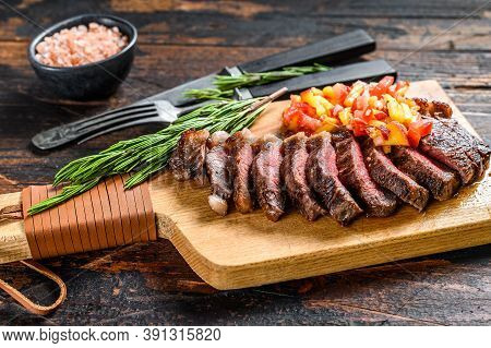 Grilled Top Sirloin Cap Or Picanha Steak On A Cutting Board With Herbs. Dark Wooden Background. Top