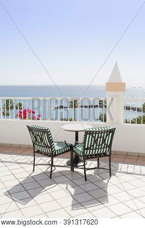 Bistro Table And Two Empty Chairs On A Balcony Overlooking The Ocean, Tenerife, Canary Islands