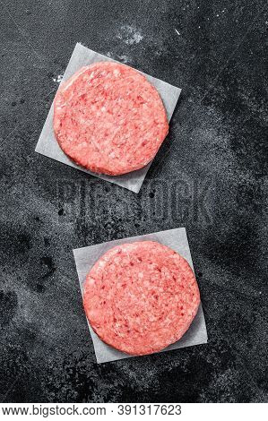 Raw Ground Meat Cutlet, Mince Beef. Burger Patties. Black Background. Top View