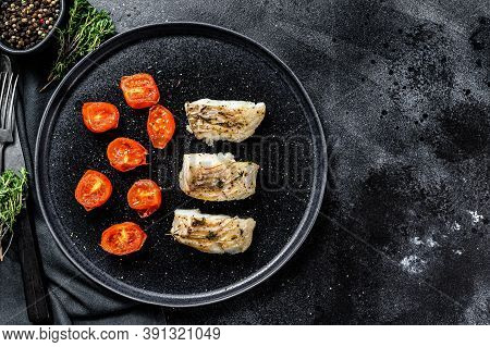 A Portion Of Grilled, Baked Pollock Or Coalfish Fillets. Black Background. Top View. Copy Space