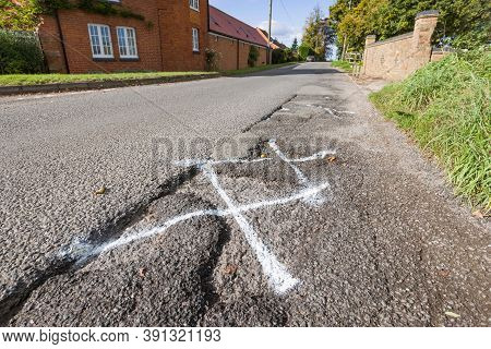 Pothole, Pot Holes In Uk Country Road Marked For Highway Maintenance