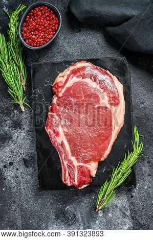 Raw Cowboy Steak. Marble Beef Meat On The Bone Ribeye. Black Background. Top View