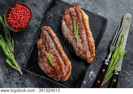 Grilled Top Sirloin Cap Or Picanha Steak On A Stone Chopping Board. Black Background. Top View