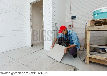 Master Is Installing Floor Ceramic Tile In A Room, Pressing Down And Leveling, Interior Finishing Of