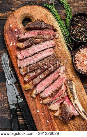 Ribeye Steak On The Bone. Grilled Beef Meat. Wooden Dark Background. Top View
