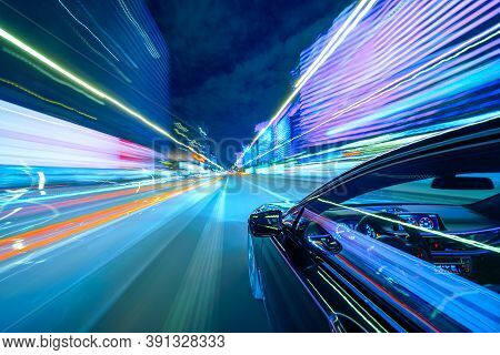 View From Side Of A Black Car Moving In A Night City, Blured Road With Lights With Car On High Speed