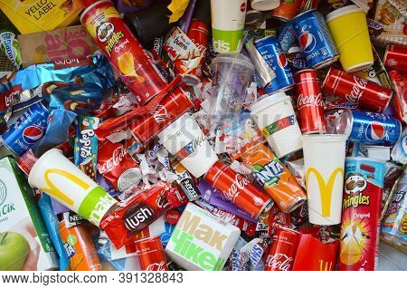 Many Wrappings And Cans From Used Products By Famous Worldwide Brands. Pattern Of Trash Of Various C