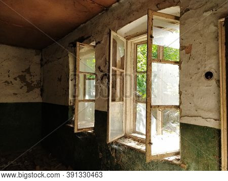 Inside Abandoned House. View On Broken Windows Without Curtain. Grunge Scene. Through The Old Wooden