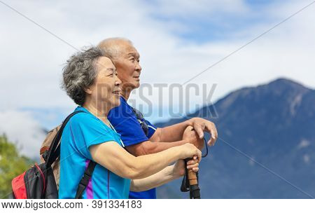 Happy Asian Senior Couple Hiking In Nature