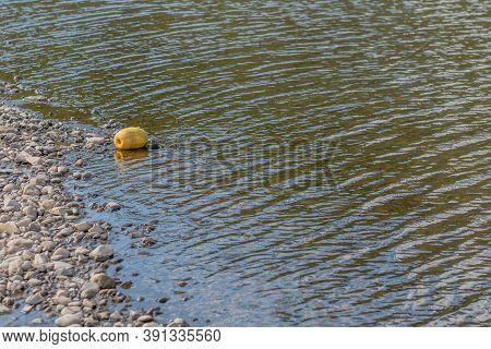 Large Yellow Styrofoam Buoy In Shallow Water Beside Riverbank.