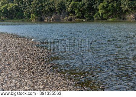 Large Piece Of Styrofoam In Shallow Water Beside Riverbank.