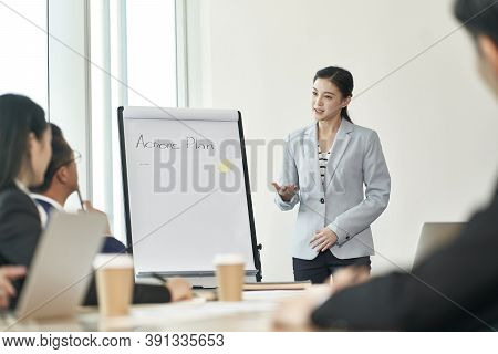 Young Asian Businesswoman Facilitating A Discussion During Team Meeting In Office