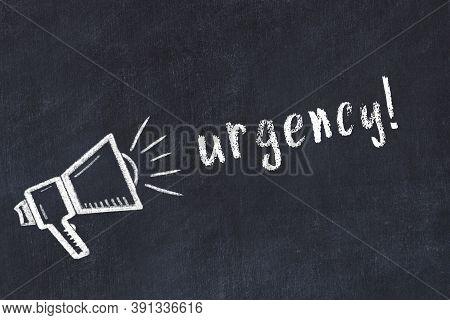 Chalk Drawing Of Loudspeaker And Handwritten Inscription Urgency On Black Desk