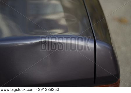Dent On The Car. Deformation Of The Car Body. Damage To The Trunk.