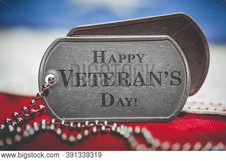 Worn US American dog tags on USA flag with Happy Veteran's Day engraved text