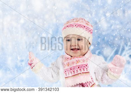 Child Playing With Snow In Winter. Little Girl In Warm Jacket And Knitted Hat Catching Snowflakes In