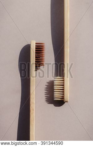Two Biodegradable Bamboo Toothbrushes On A Beige Background With Contrasting Shadows.