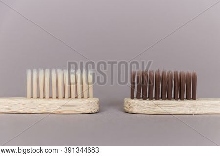 Two Biodegradable Bamboo Toothbrushes On A Beige Background.