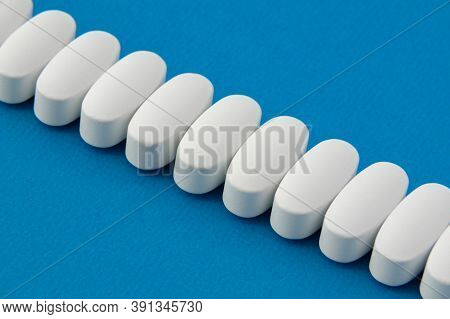 White Pills Tablets On Blue Background With Copy Space
