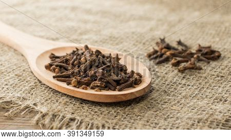 A Spice Of Dried Cloves Lies On A Wooden Spoon And Is Scattered On Old Wooden Boards. Spices Cloves