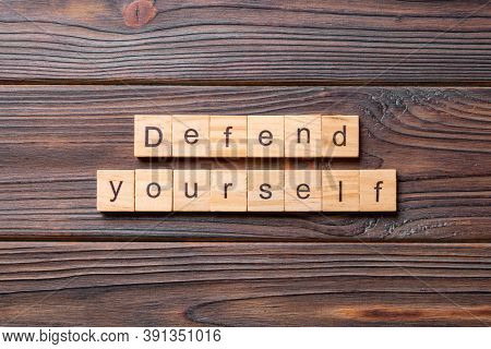 Defend Yourself Word Written On Wood Block. Defend Yourself Text On Cement Table For Your Desing, Co
