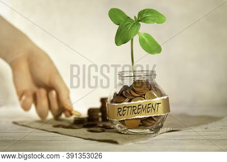Retirement. Glass Jar With Coins And A Plant, In The Background A Female Hand Puts Coins Near A Glas