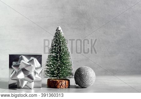 Minimalistic Christmas Composition With Decorative Fir Tree, Wooden Sledge, Gift And Ball On Grey Ba