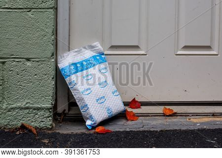 NORWALK, CT, USA - OCTOBER 24, 2020: Illustrative images package from Amazon Prime delivery outside next front door