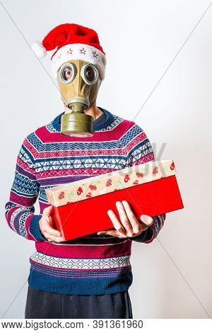 Anonymous Person In Christmas Clothes With A Gift In The Hand And Face Protection
