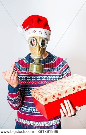 Person In Christmas Clothes And Gas Mask With Gift In The Hand Showing On Middle Finger Fuck You