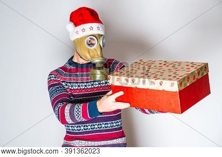 Person In Gas Mask With Christmas Hat And Sweater Opening Gift On Light Background.
