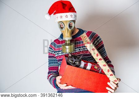 Person In Gas Mask Opening The Christmas Gift With Cat In Clothes Inside