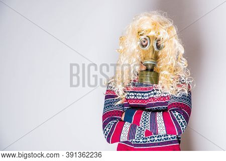 Travesty Man With Long Curly Blond Hair In Gas Mask On Light Background With Copy Space