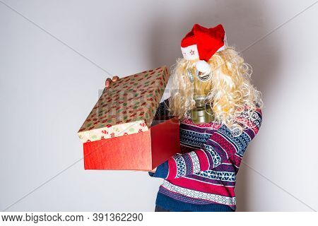 Transgender Person In Christmas Clothes And Face Protection Looking Into The Opening Gift Box