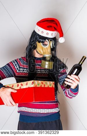 Person With Long Black Hair In Gas Mask And Christmas Hat With Gift And Bottle Of Wine In Hands On L