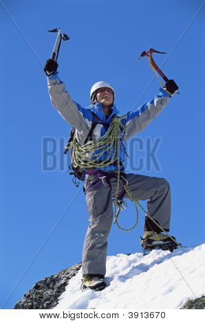 Man Mountain Climber Celebrating Reaching Top Of Snowy Mountain