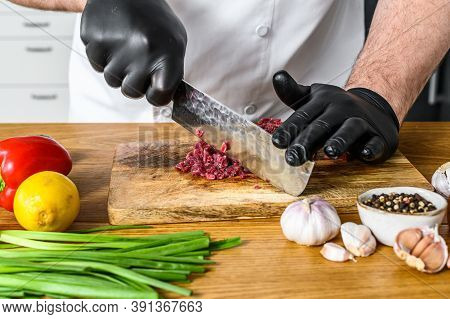Man Cutting Raw Beef Meat. A Chef In Black Gloves. Concept Of Cooking Beef Tartare