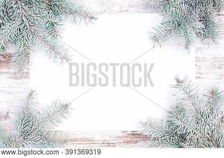 Nordic Rustic Style Christmas Background With Snow Covered Spruce Twigs And Blank Paper With Copy Sp
