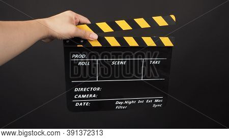 Hand Is Holding Yellow And Black Color Movie Slate.it Is Used In Video Production And Film Industry