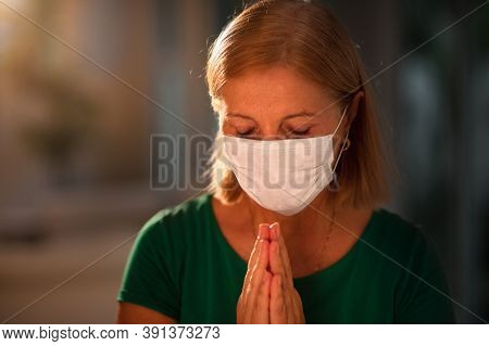 Pray For Xxx. Woman In Face Mask Praying. Senior Patient In Hospital Chapel Or Church During Coronav