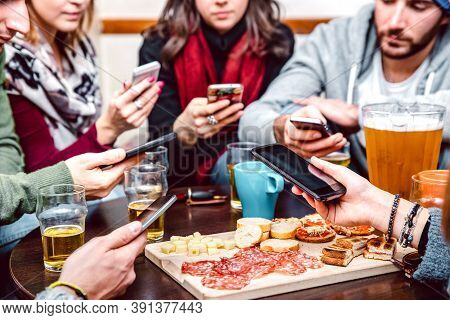 Side Angle View Of Hands With Cellphones At Beer Bar Restaurant - People Sharing Time Together With