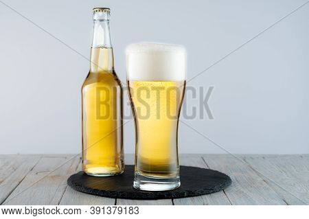A Glass Of Light Beer On A Tray. Bottle And Glass Of Light Beer. Beer On The Table.