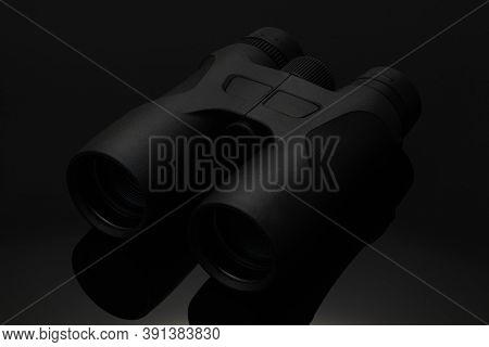 Black Binocular Isolated On Black Background. Hi Tech Black Binocular On The Black Glass Table. Stud