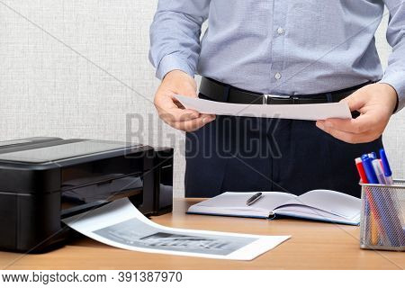 Businessman Analyzing Investment Charts With Printer. Man Using A Printer In Office.