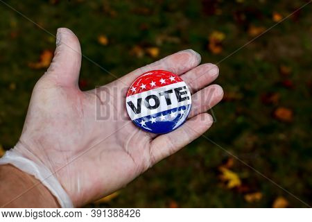 Hand with protective glove showing vote pin