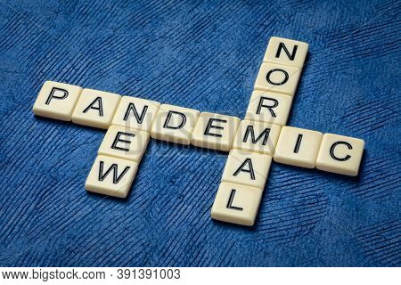 pandemic, new normal crossword in ivory letter tiles against textured paper, changes in business and lifestyle due to coronavirus outbreak